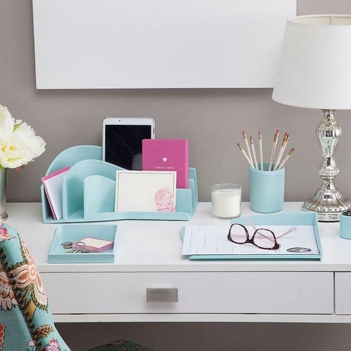 blue desk organisers, grey wall, white desk, white flower bouquet, work desk decor