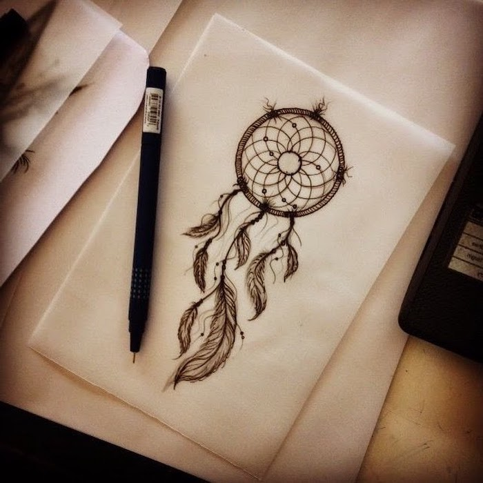 black and white drawing, white paper, wooden table, black pencil, disney dream catcher