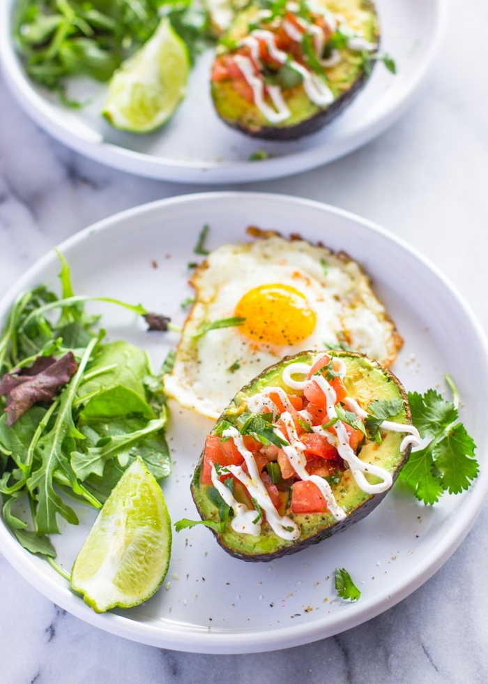 halved avocado, filled with chopped tomatoes, on white plate, fried egg, green salad, breakfast recipes