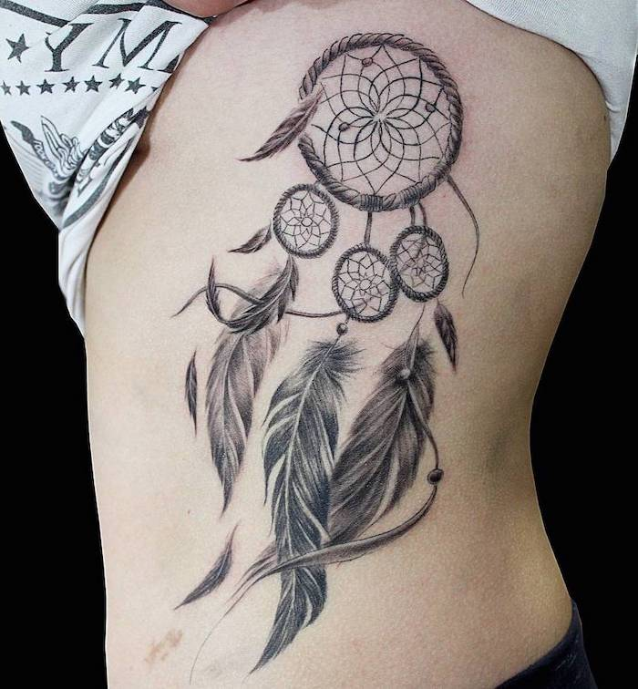 side of the stomach tattoo, disney dream catcher, black background, white t shirt