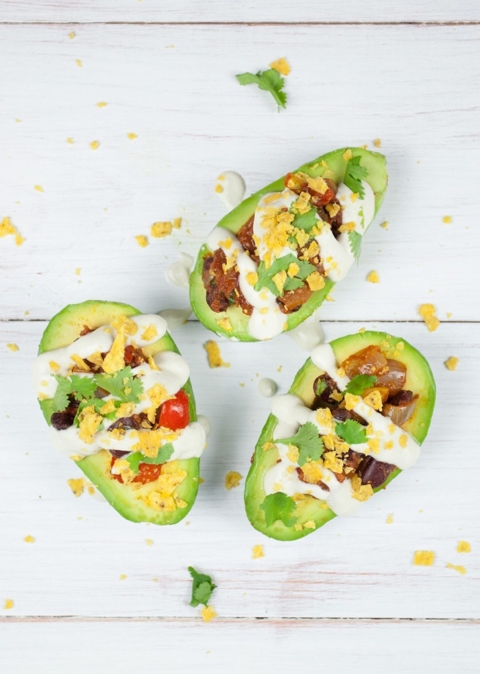 halved avocados, filled with eggs, bacon and tomatoes, sour cream dressing, breakfast finger foods, wooden table