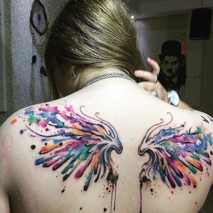 watercolor tattoo, back tattoo, woman with blonde hair, wings neck tattoo, blurred background