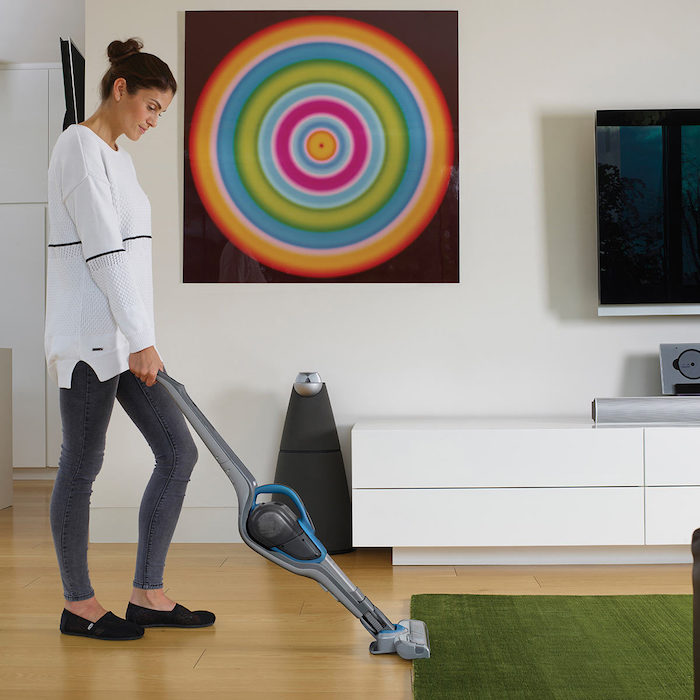 woman cleaning, white blouse, grey trousers, best vacuum cleaner, green carpet, wooden floor