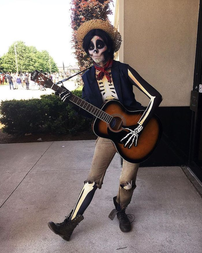 woman holding a guitar, easy halloween costumes for guys, skeleton costume, skeleton face make up