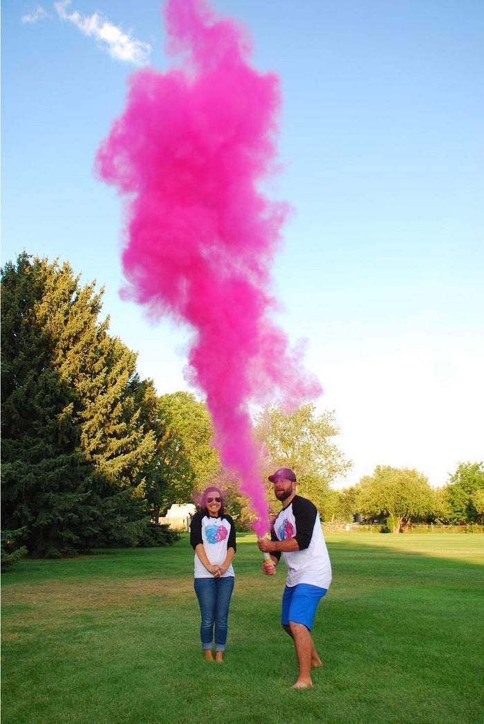 man and woman, standing in a field, man holding, pink smoke bomb, gender reveal ideas