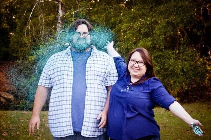woman smiling, throwing blue glitter, in a man's face, gender reveal decorations