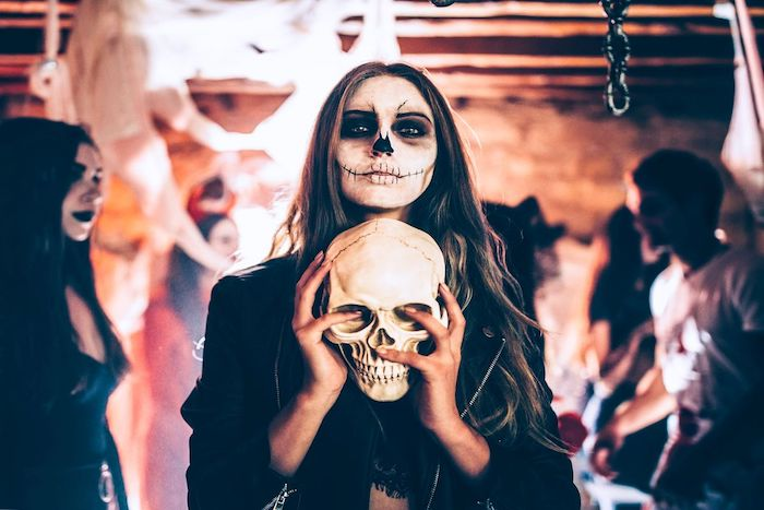 woman holding a skeleton, calavera make up, last minute halloween costumes, long brown hair