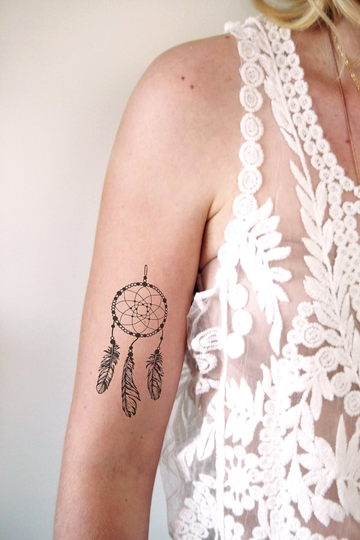 woman wearing a white top, dream catcher tattoo ideas, inside arm tattoo, white background