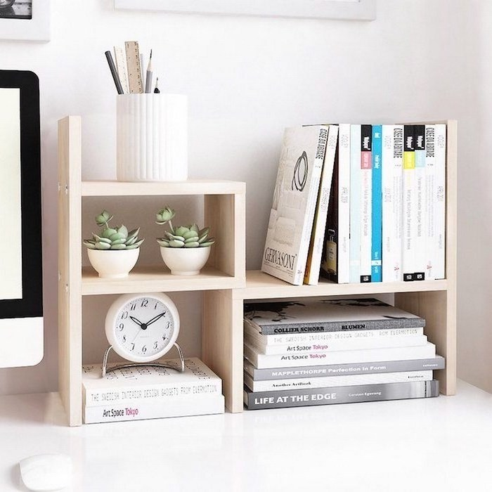 wooden desk organiser, ideas for decorating your office at work, lots of books, potted succulents, pencil holder
