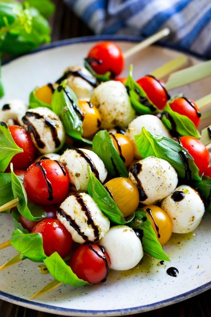 cherry tomatoes, basil and mozzarella, on wooden skewers, breakfast finger foods, white plate