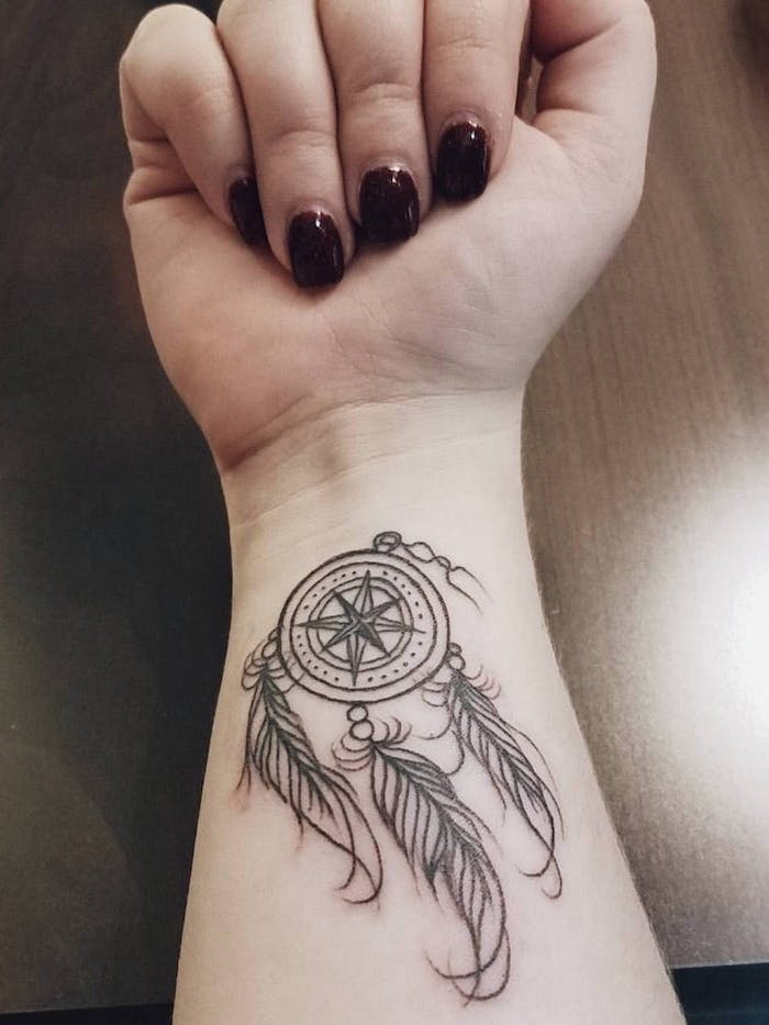 wooden table, dark red nail polish, dream catcher tattoo ideas, wrist tattoo