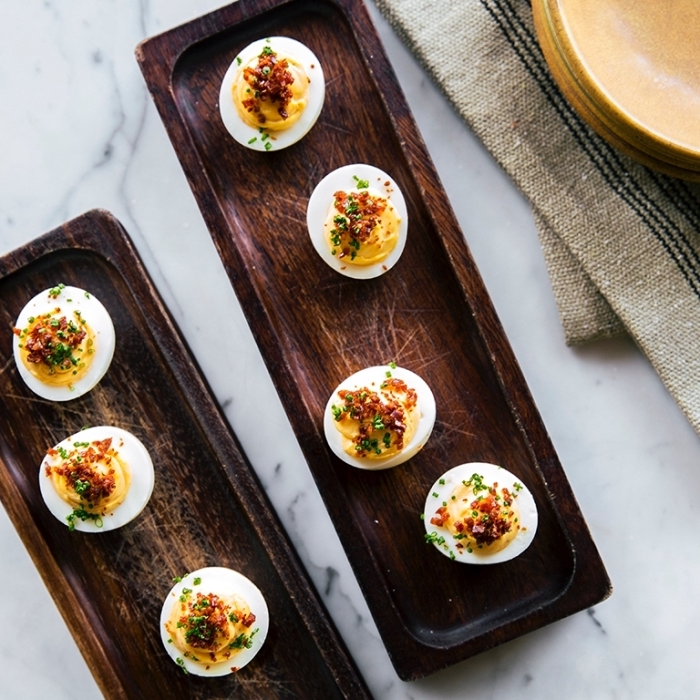breakfast recipe ideas, wooden plates, eggs filled with mayo, chives on top, marble countertop