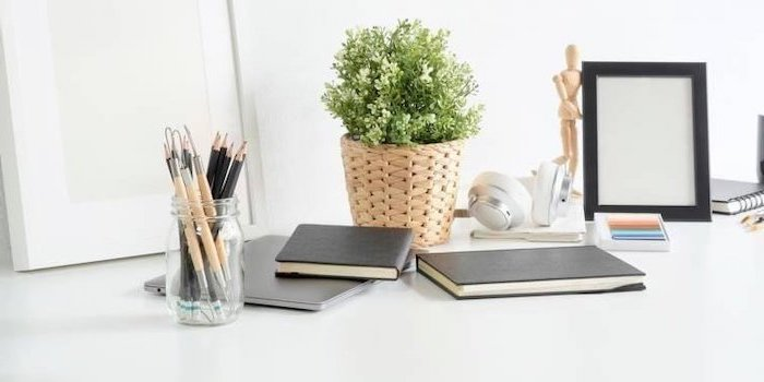 black notebooks, on white desk, potted plant, wooden pot, office cubicle accessories, glass pencil holder