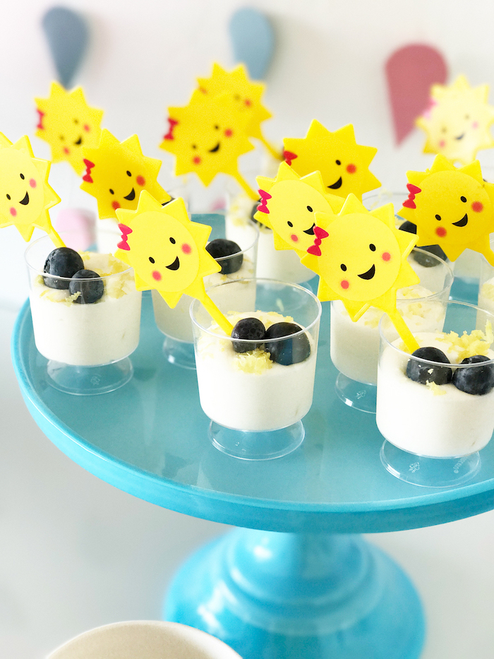 yoghurt with lemon zest, blueberries on top, sun cake toppers, on blue cake stand, baby shower themes for girls