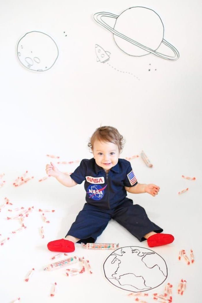 little boy, sitting on the floor, dressed in a nasa onesie, halloween costumes for girls, planets drawn on the wall