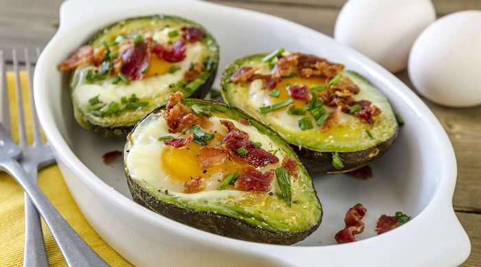 halved avocados, filled with eggs, chives and bacon on top, white casserole, low carb breakfast ideas, yellow table cloth