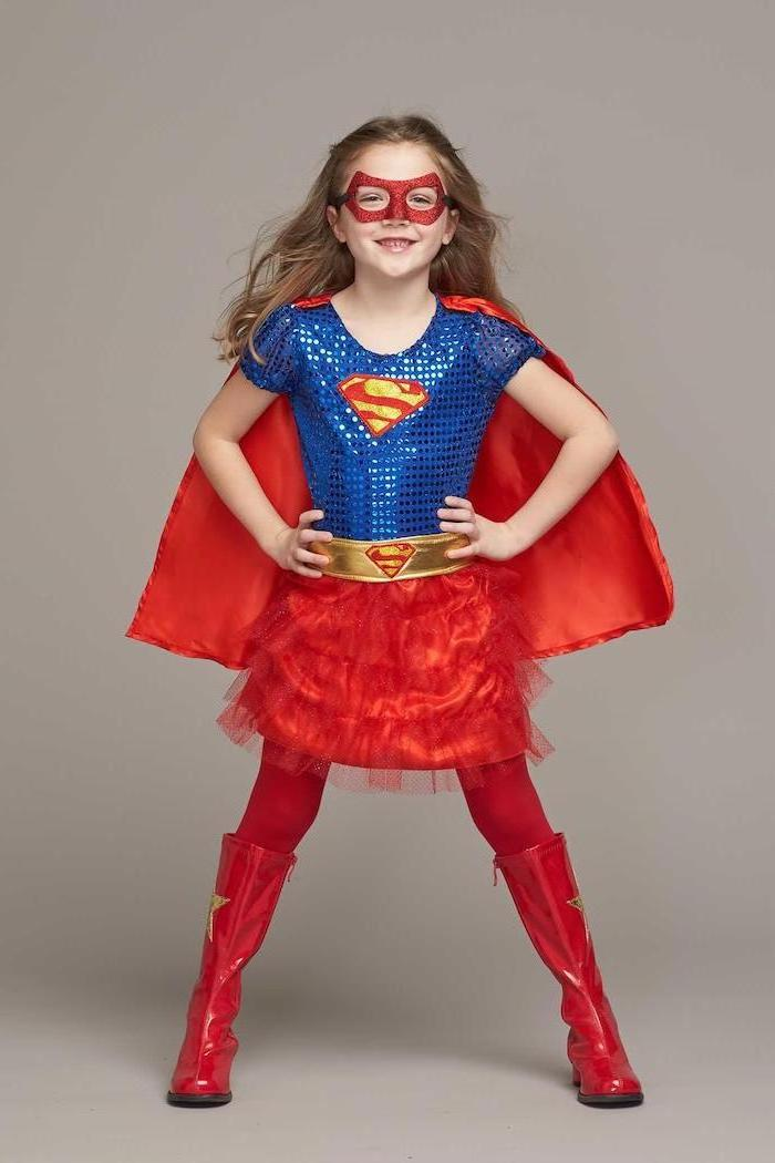 halloween costumes for girls, girl dressed as supergirl, blue sequinned top, red tulle skirt, red cape