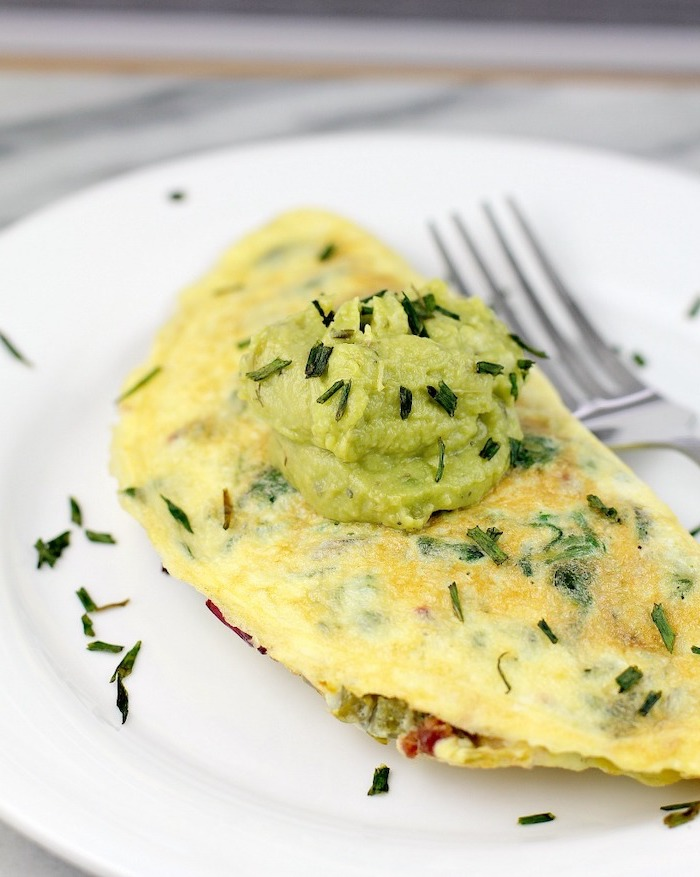 bacon jalapeno omelet, easy keto breakfast, chives and guacamole sauce on top, white plate, silver fork