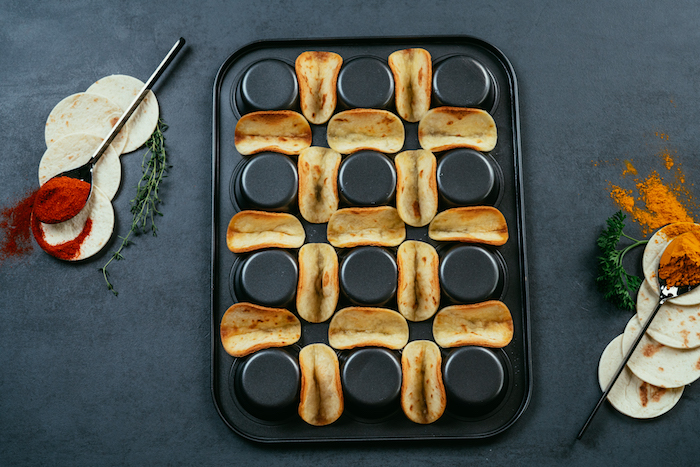 spoons of seasoning, how to make tacos, tortilla wraps, arranged on a black, muffin tray, black table