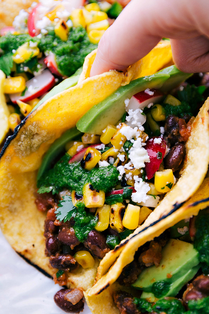 tortilla wraps, filled with beef, corn and turnip, avocado slices, ground beef tacos