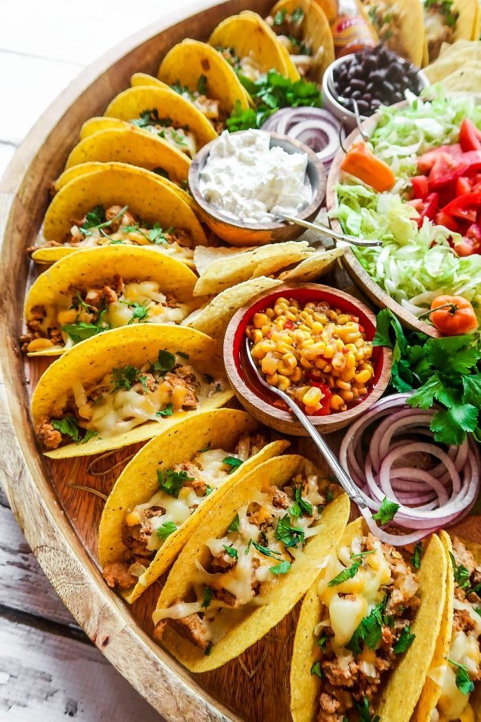 mini tacos, arranged on a large, wooden tray, ground beef taco recipe, glass bowls, different ingredients