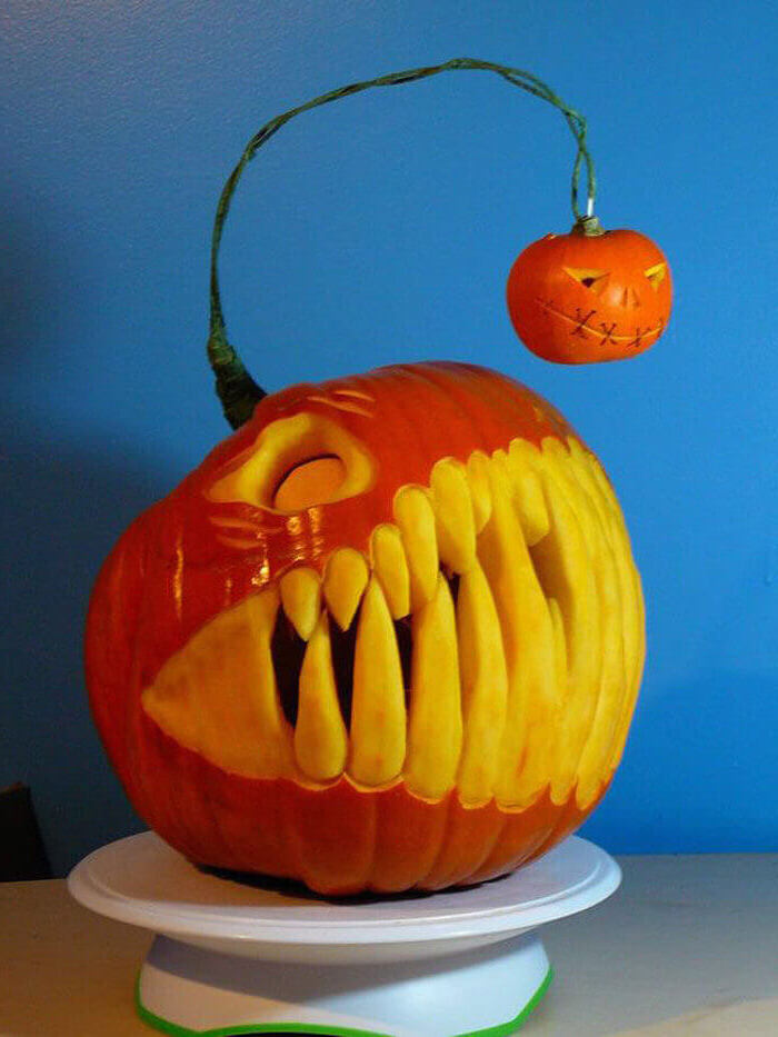 pumpkin with large teeth, carved into it, another smaller pumpkin hanging, funny pumpkin carving, blue wall