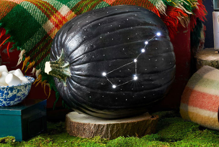 pumpkin carving ideas, pumpkin painted in black, constellation carved into it, sitting on a wooden log, on top of moss