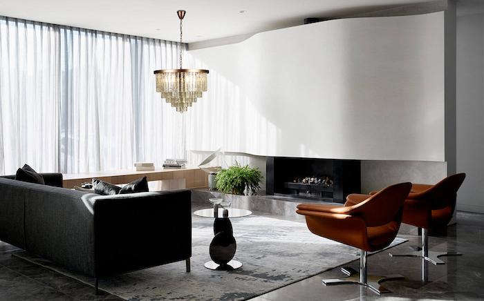 black sofa, black throw pillows, orange armchair, large carpet, white curtains, murano glass chandelier