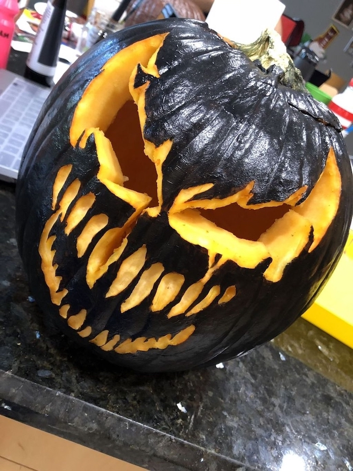 large pumpkin, painted in black, venom movie inspired, funny pumpkin carving, granite countertop
