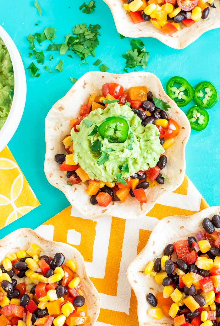 tortilla bowls, filled with corn, chopped vegetables, black beans, best taco seasoning, turquoise table