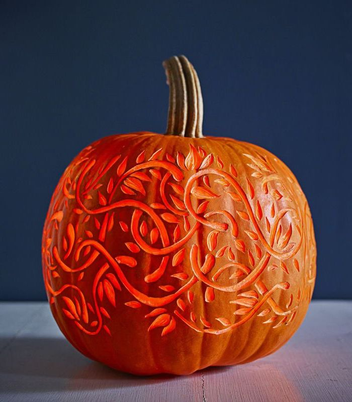 blue wall, funny pumpkin carving, floral motifs, carved into a pumpkin, lit by a candle