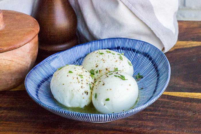 three boiled eggs, with thyme and butter, in a blue and white bowl, keto breakfast recipes, wooden table