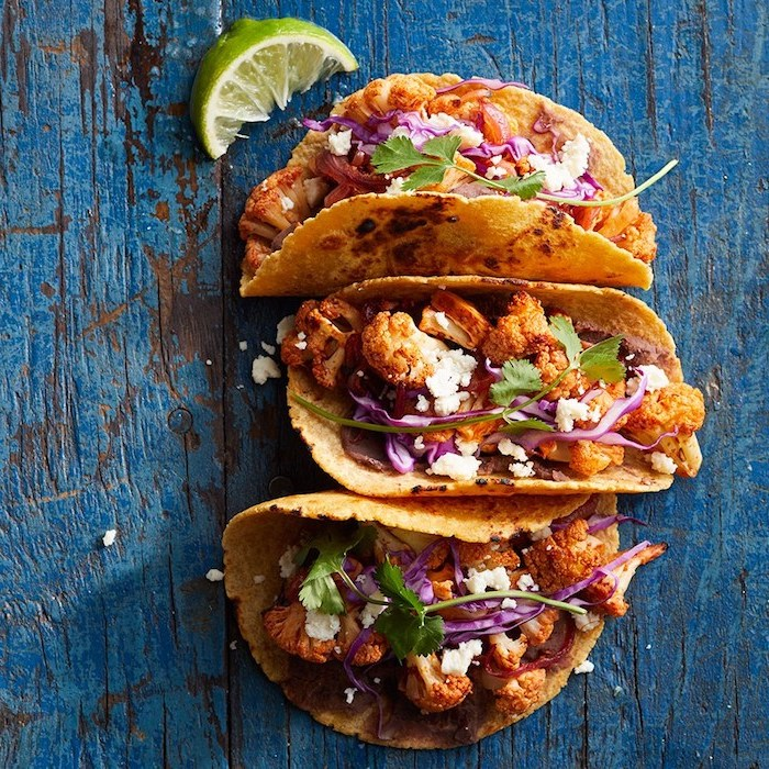 three tacos, with cauliflower, arranged on a blue, wooden table, how to cook taco meat, lime slice