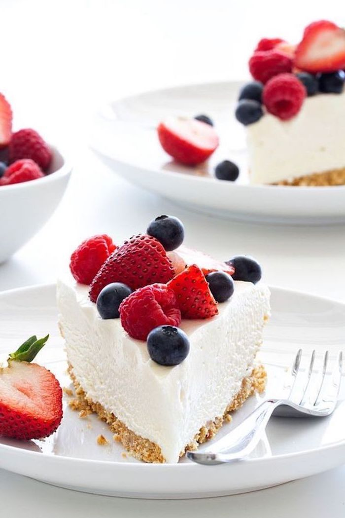 no bake desserts, cheesecake slices, on a white plate, with strawberries, blueberries and raspberries