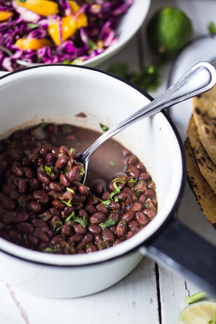 black beans, in a white bowl, white wooden table, taco toppings, chopped cabbage, in a white bowl