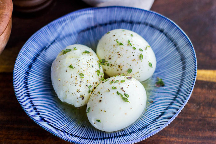 three boiled eggs, with thyme and butter, easy keto meals, blue and white bowl, wooden table