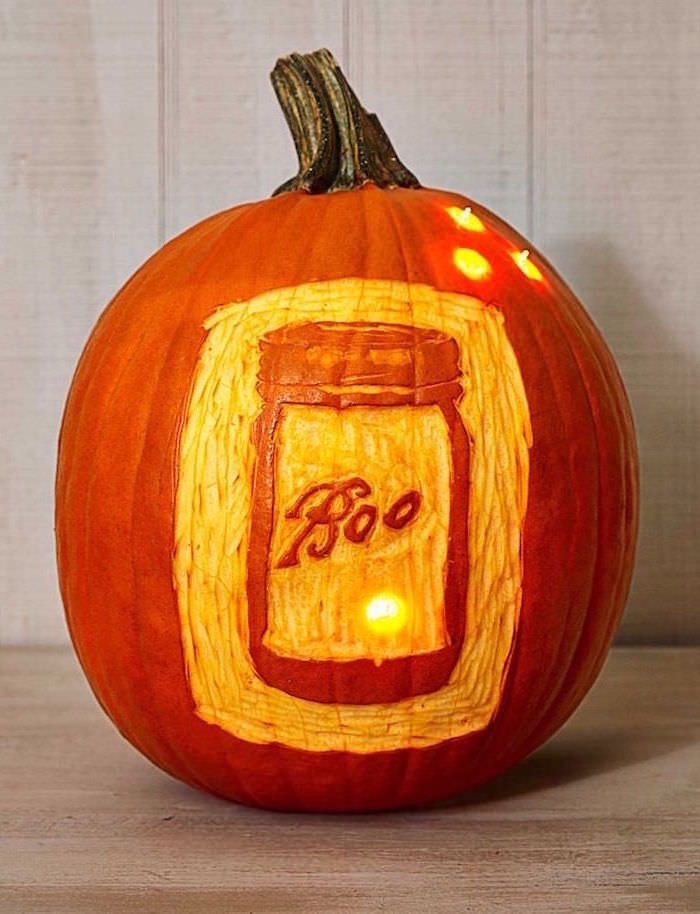 boo mason jar, carved into a pumpkin, lit by candles, wooden background, jack o lantern designs