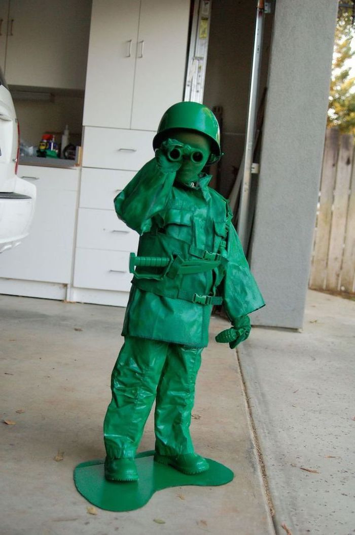 little boy, dressed as a toy soldier, halloween costumes for kids, all green costume, white cupboards, in the background