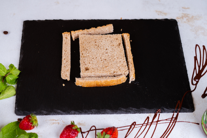 bread slice with the crust cut off, placed on black cutting board, french toast, strawberries and chocolate around it