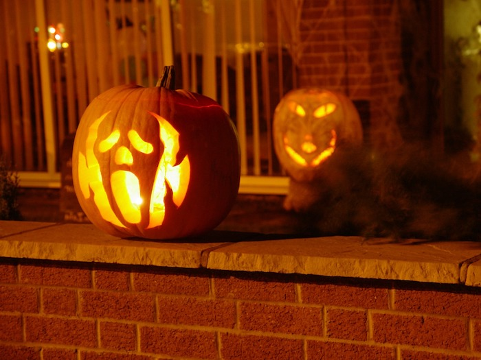 two pumpkins, ghost face carved into one, cat face carved into the other, pumpkin carving ideas, brick wall