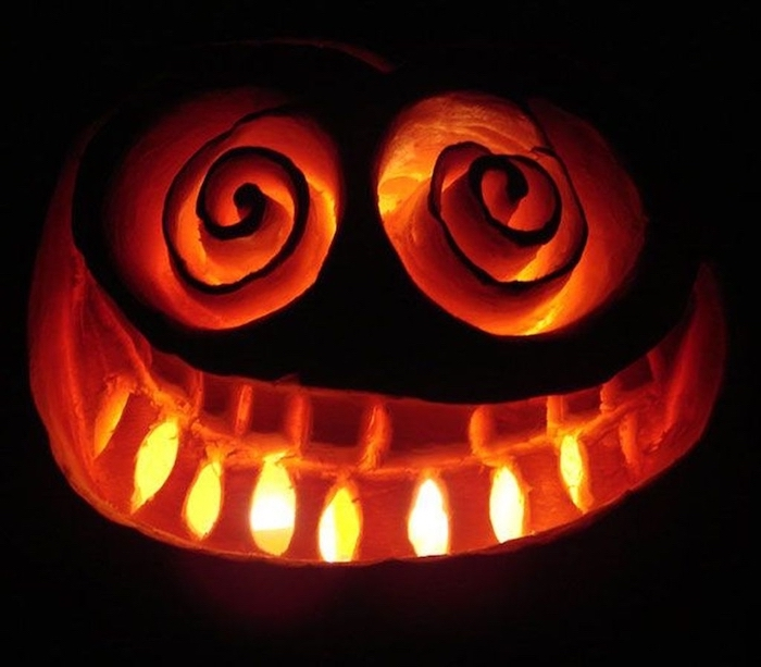 black background, jack o lantern designs, face carved into a pumpkin, lit by candles