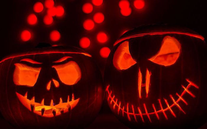 two pumpkins, lit by candles, scary faces, carved on them, black background, pumpkin carving ideas