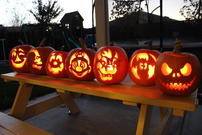 different pumpkins, different faces carved on them, on a wooden table, pumpkin carving ideas, lit by candles