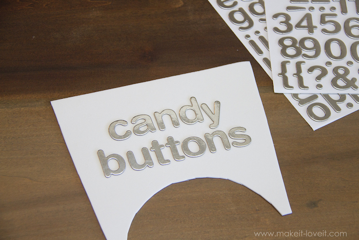 silver letters, candy buttons, glued to white paper, baby costumes for boys, wooden table