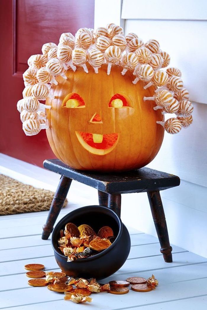 lollipops stuck onto a pumpkin, on a black wooden stool, jack o lantern designs, candies scattered around