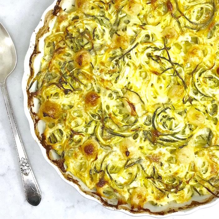 zoodles casserole, zucchini spaghetti recipe, white ceramic baking tray, silver spoon, marble countertop