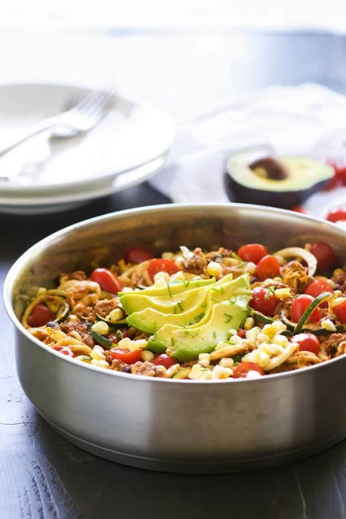 taco zoodles, how to make zucchini noodles, cherry tomatoes, avocado slices, corn and turkey, in a skillet