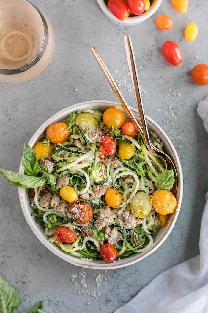 cherry tomatoes, zucchini spaghetti recipe, chicken fillet, basil leaves, in a white bowl, granite countertop