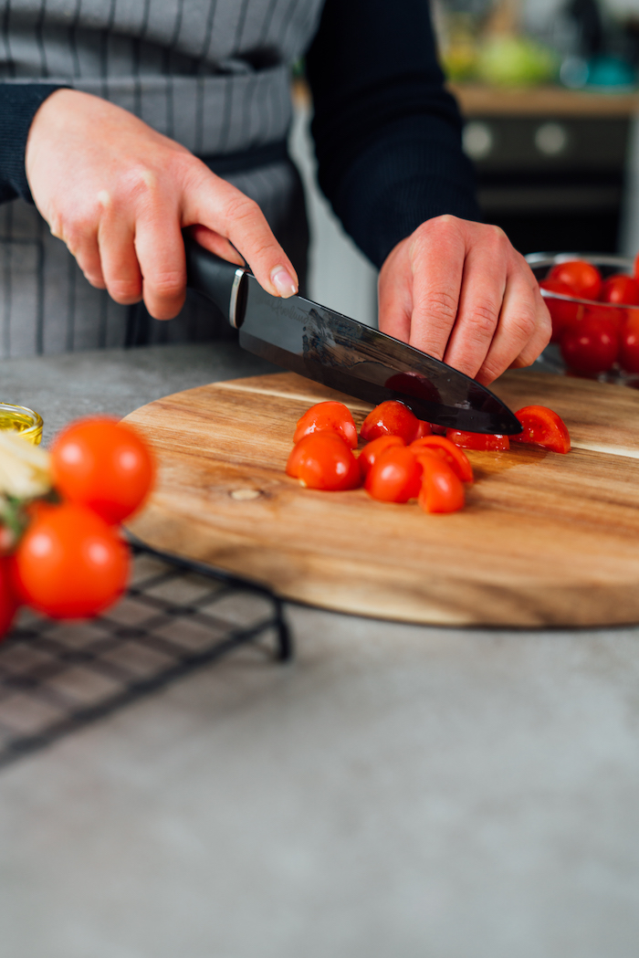cherry tomatoes being halved with black knife on wooden cutting board how to make zoodles