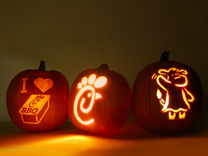 chick fil a inspired, three pumpkins, lit by candles, jack o lantern designs, dark background